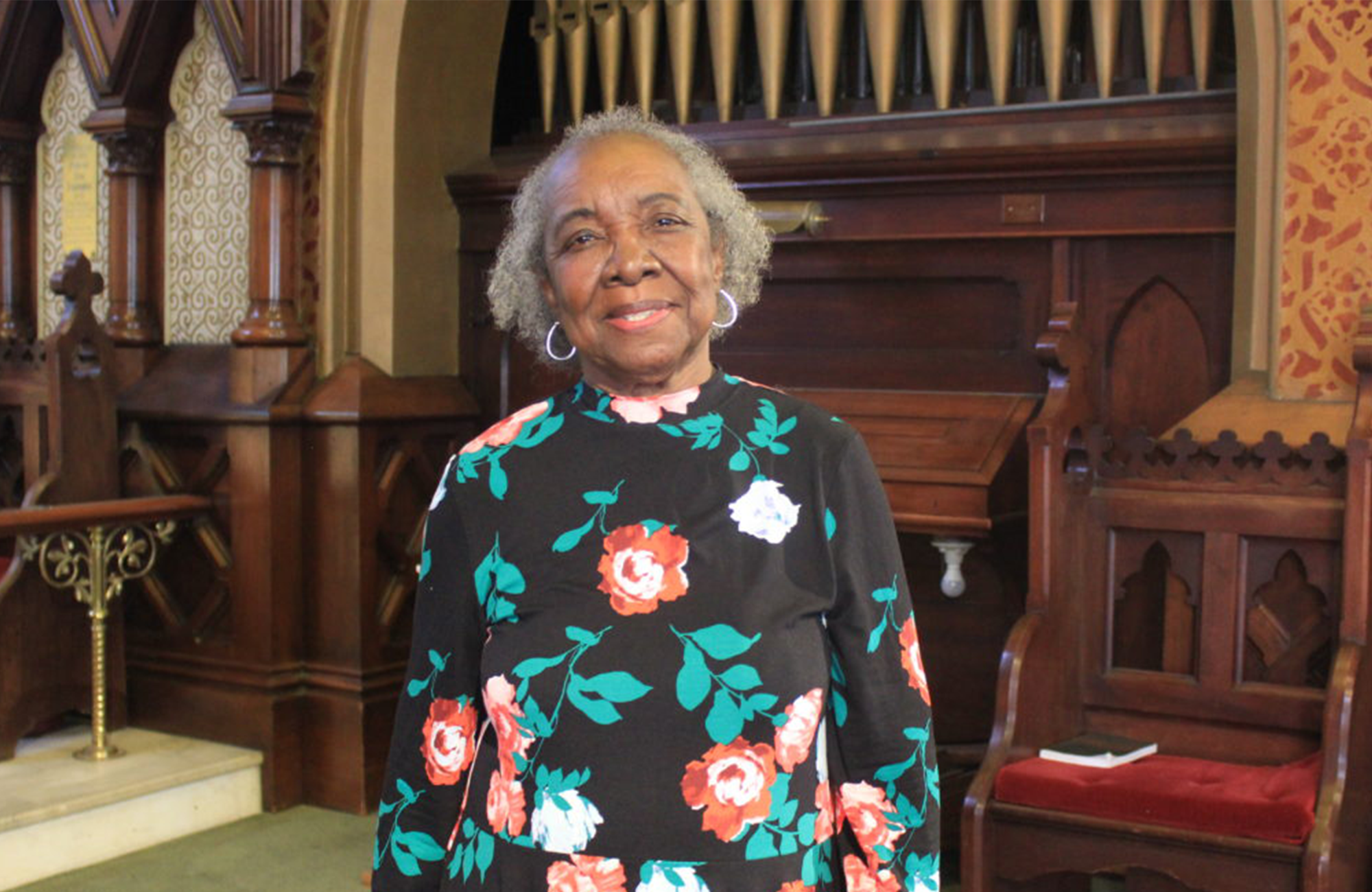 Image of Dr. Joan Hillsman in front of church organ pipes
