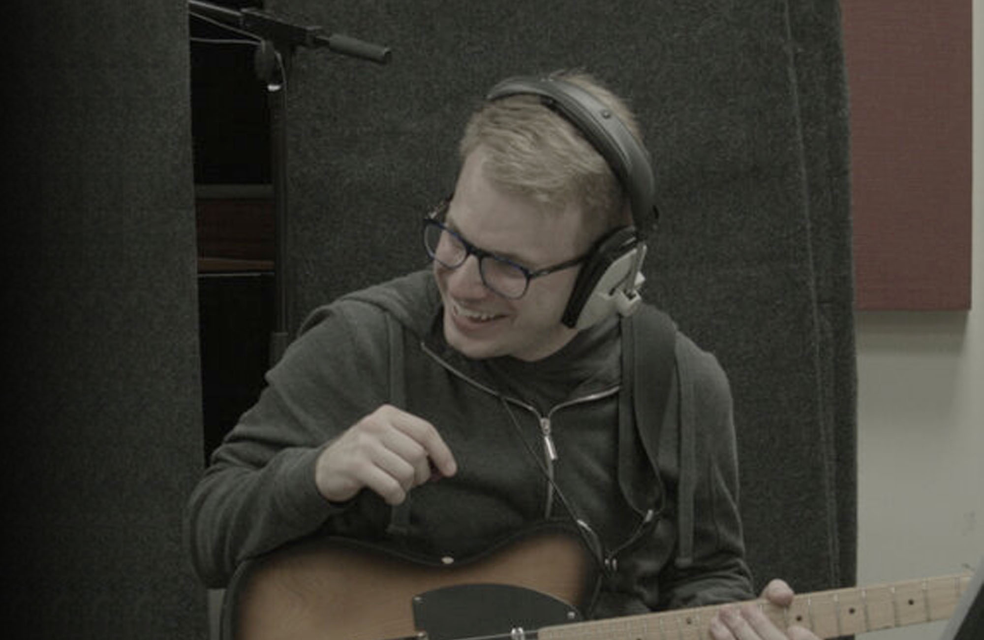 image of Chris Cresswell holding guitar and wearing headphones