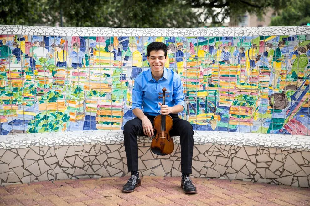Ruben Rengel sitting on a bench with violin